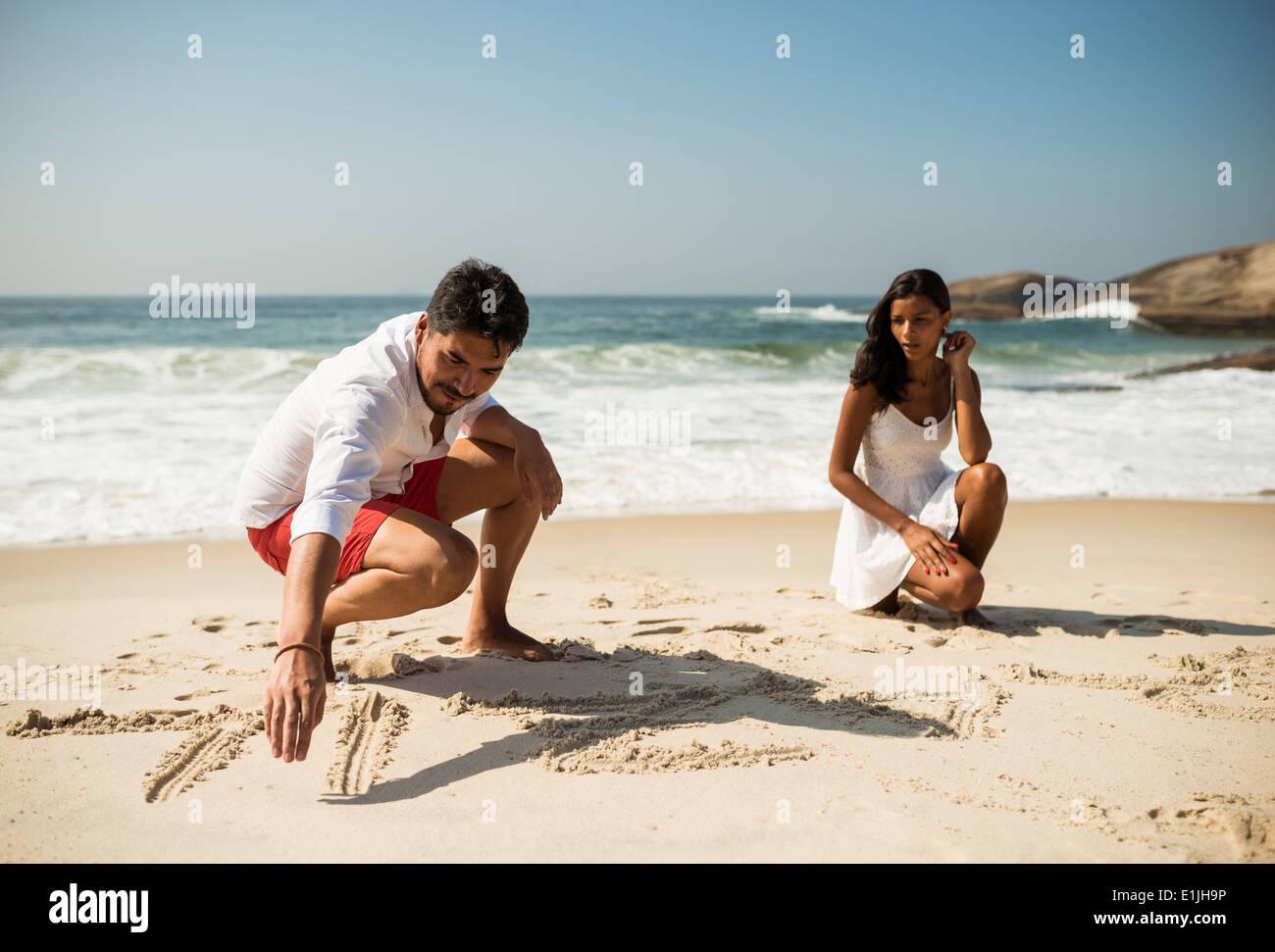 Couple writing in sand on Arpoador beach, Rio De Janeiro, Brazil - Stock Image