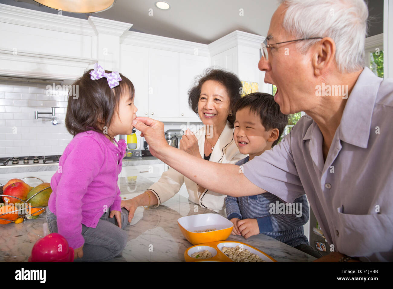 Grandfather feeding snack to toddler granddaughter in kitchen - Stock Image