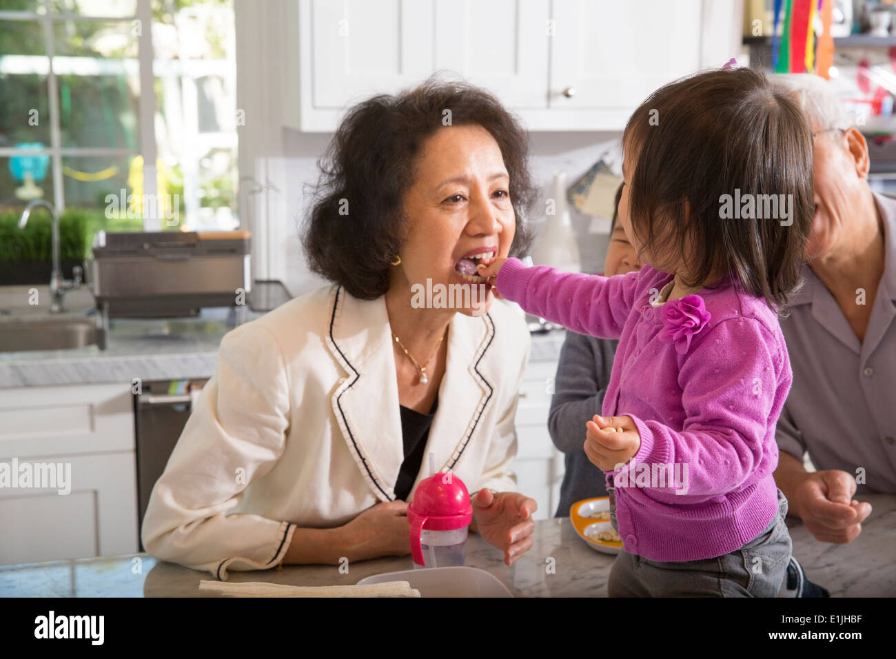 Female toddler feeding snack to grandmother in kitchen - Stock Image