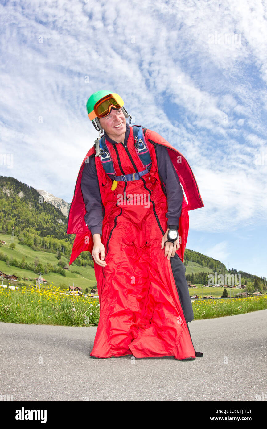 Happy and relieved young man after landing in wingsuit - Stock Image