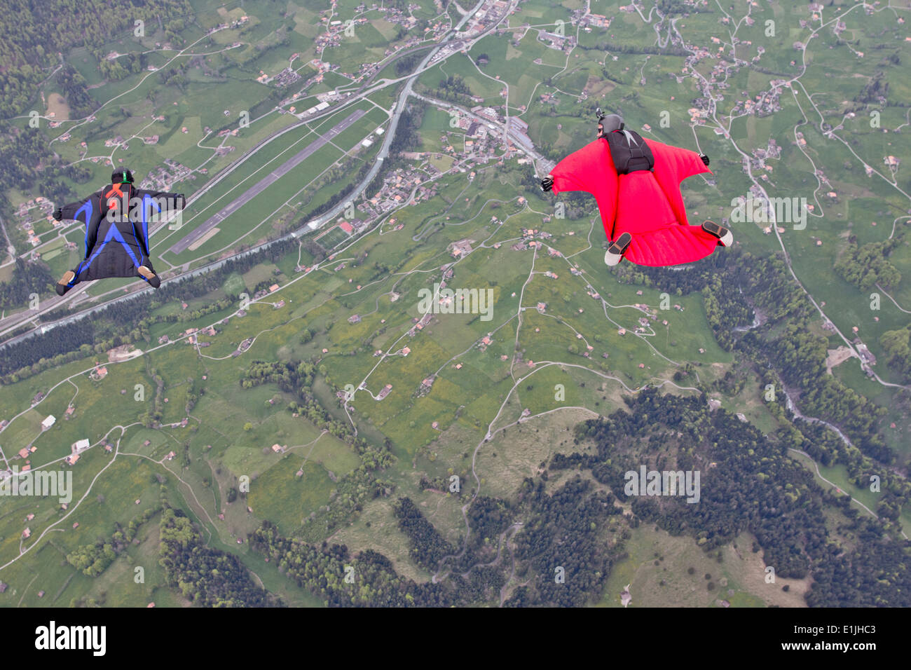 Two men flying above fields in wingsuits - Stock Image