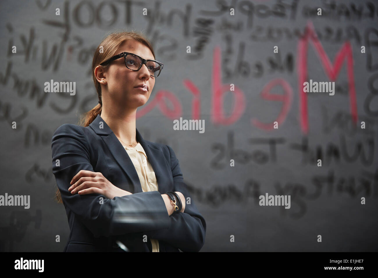 Portrait of businesswoman wearing jacket with writing - Stock Image