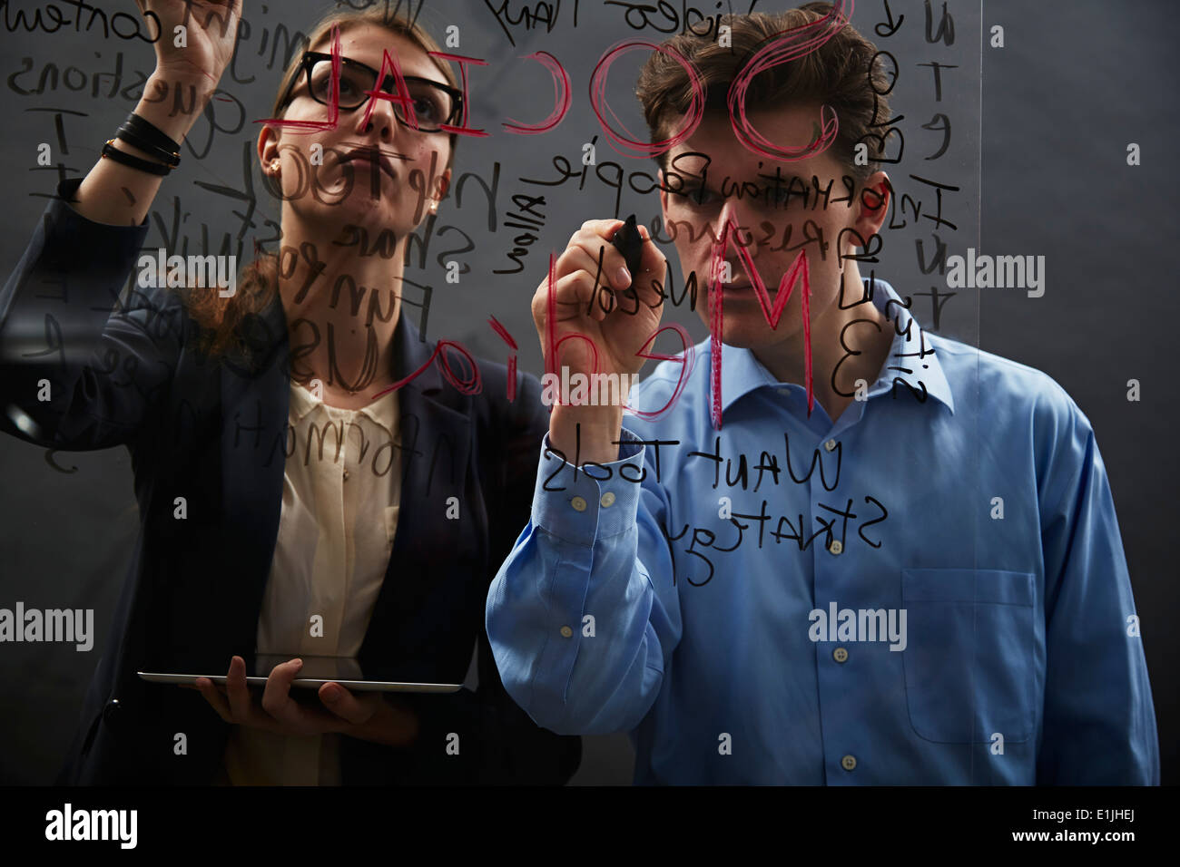 Business colleagues writing on glass - Stock Image