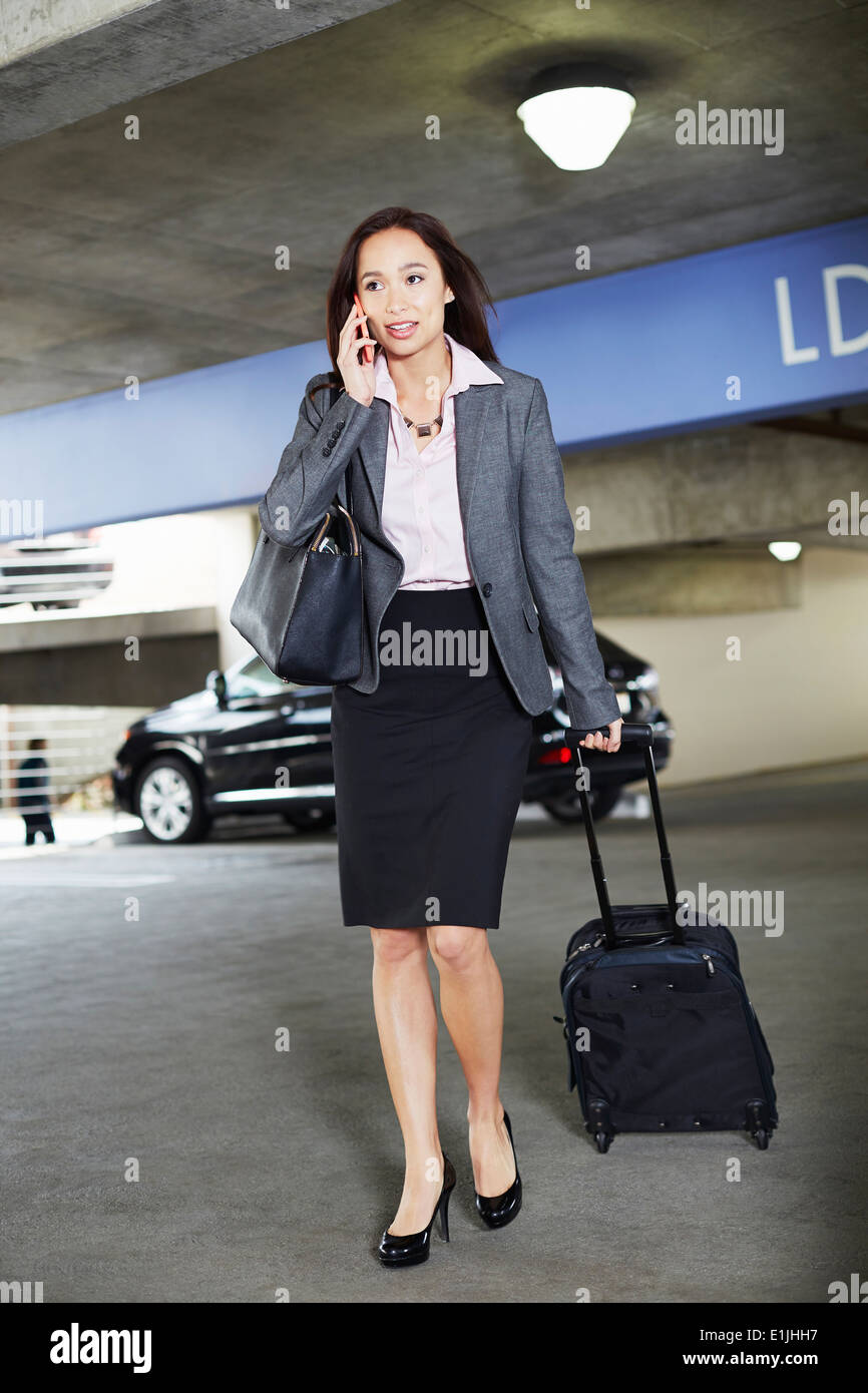 Young female businesswoman with wheeled suitcase in car park - Stock Image