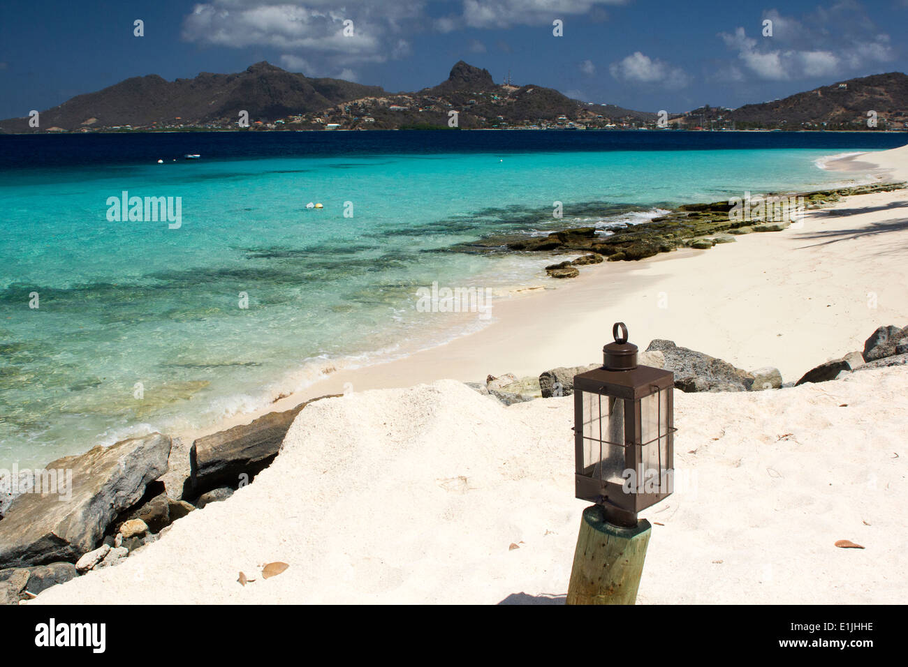 Palm Island Beach with Lamp, Turquoise Caribbean Ocean and View of Union Island. Saint Vincent and the Grenadines. - Stock Image
