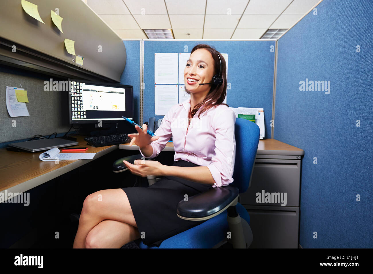 Young female office worker using bluetooth headset in office - Stock Image