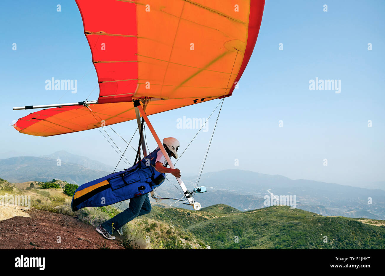 Hang glider pilot taking off - Stock Image