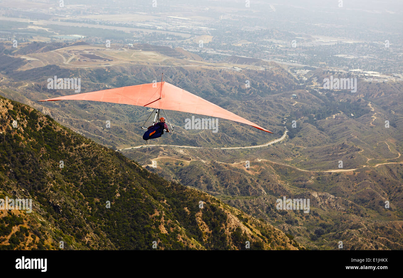 Man flying hang glider over valley - Stock Image