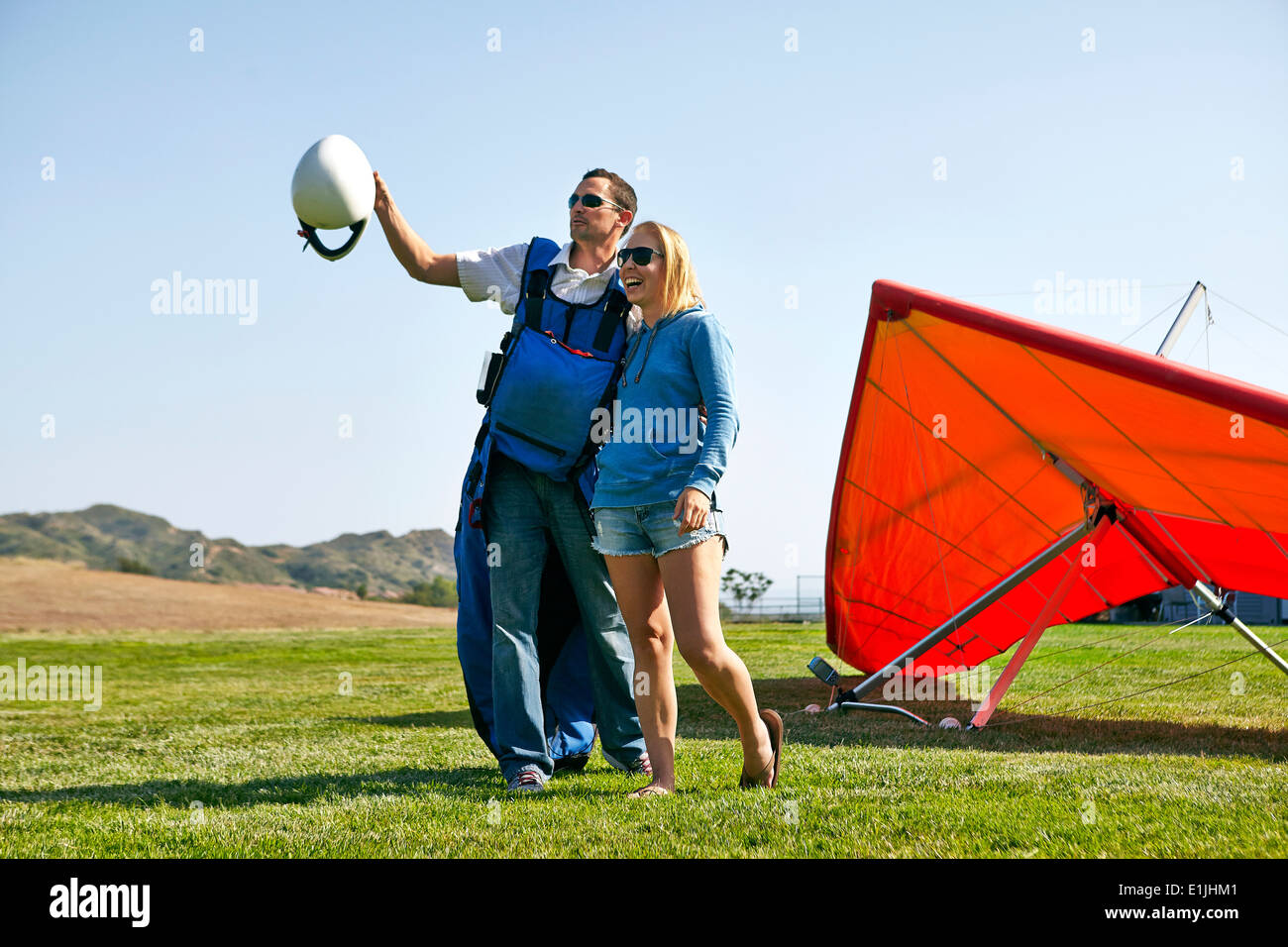 Couple enjoying view, hang glider in background - Stock Image
