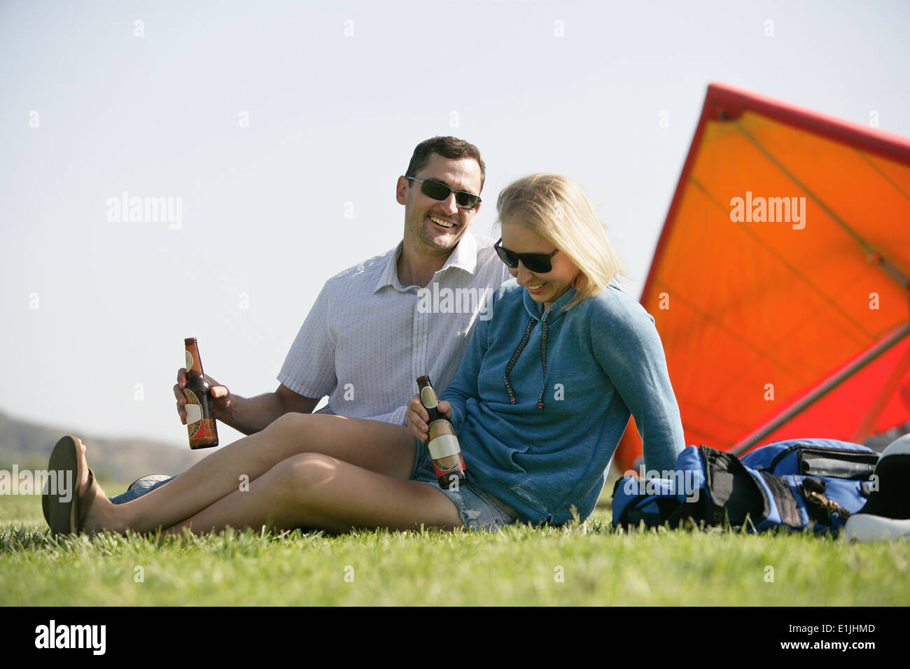 Couple relaxing with beer, hang glider in background - Stock Image