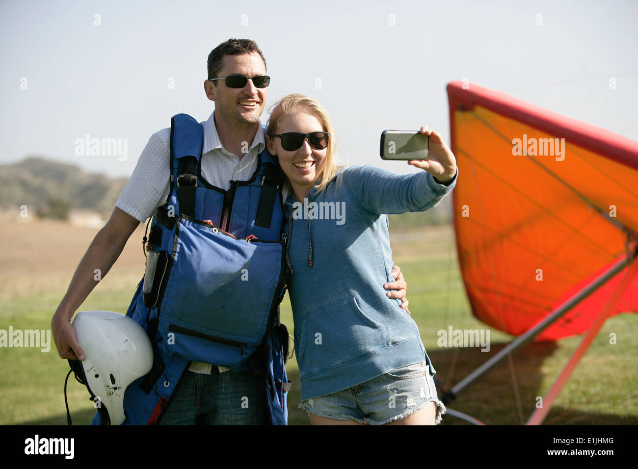 Couple taking selfie, hang glider in background Stock Photo