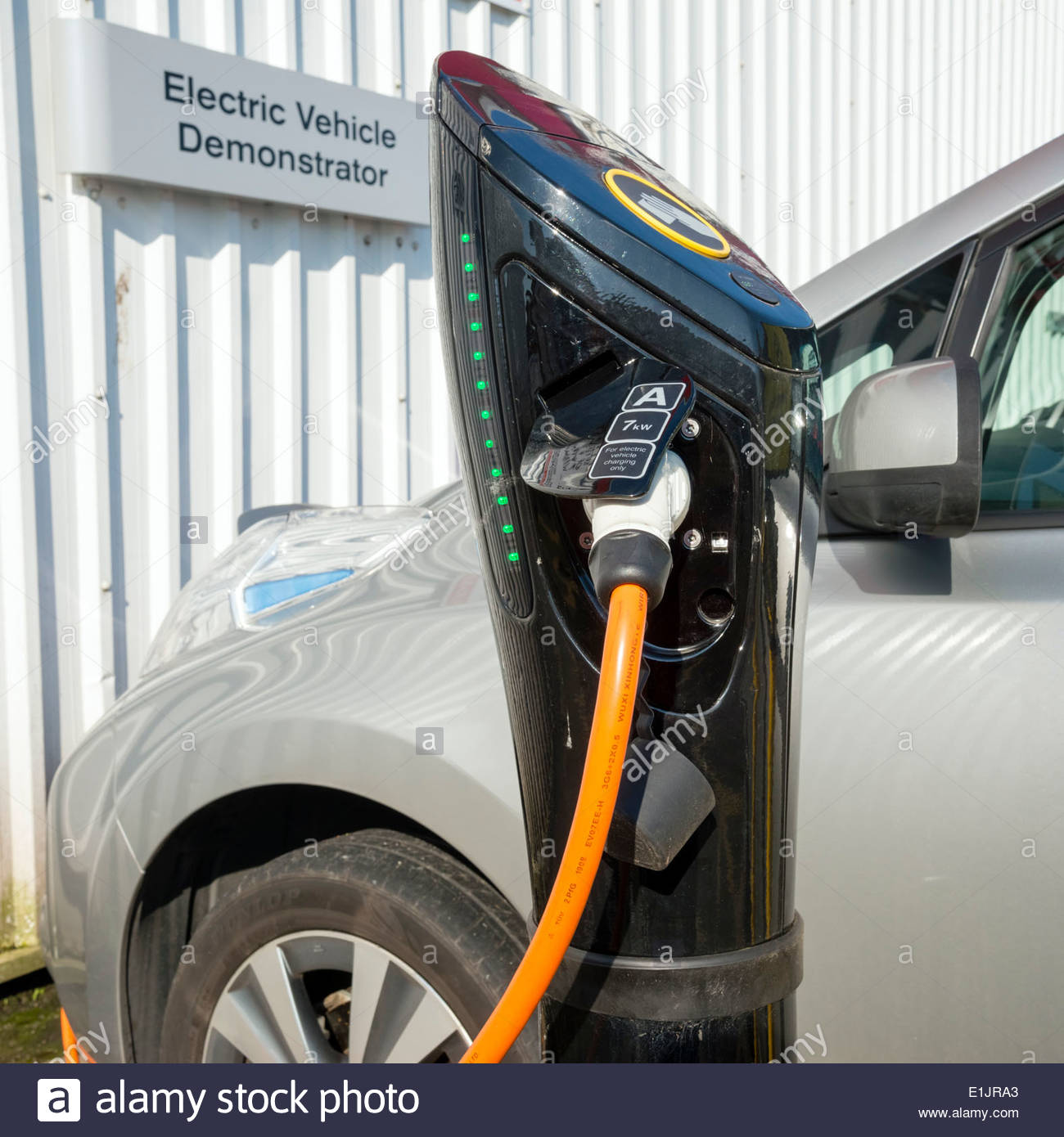 Electric car demonstrator on charge at a Nissan garage, UK - Stock Image