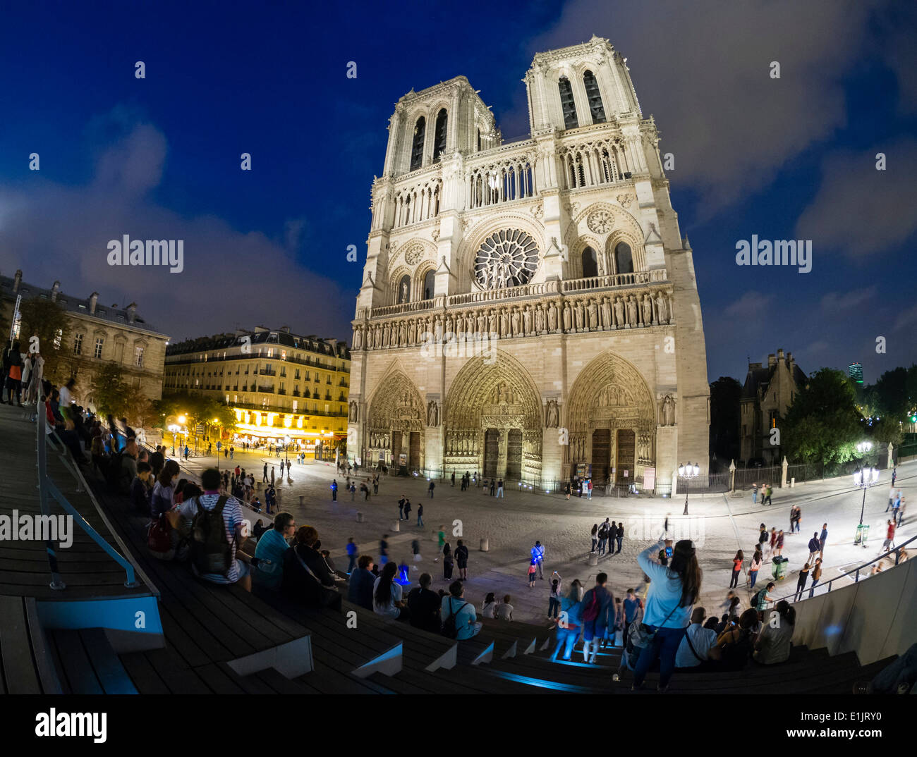 Tourists visit Notre Dame cathedral in Paris late in the evening. - Stock Image