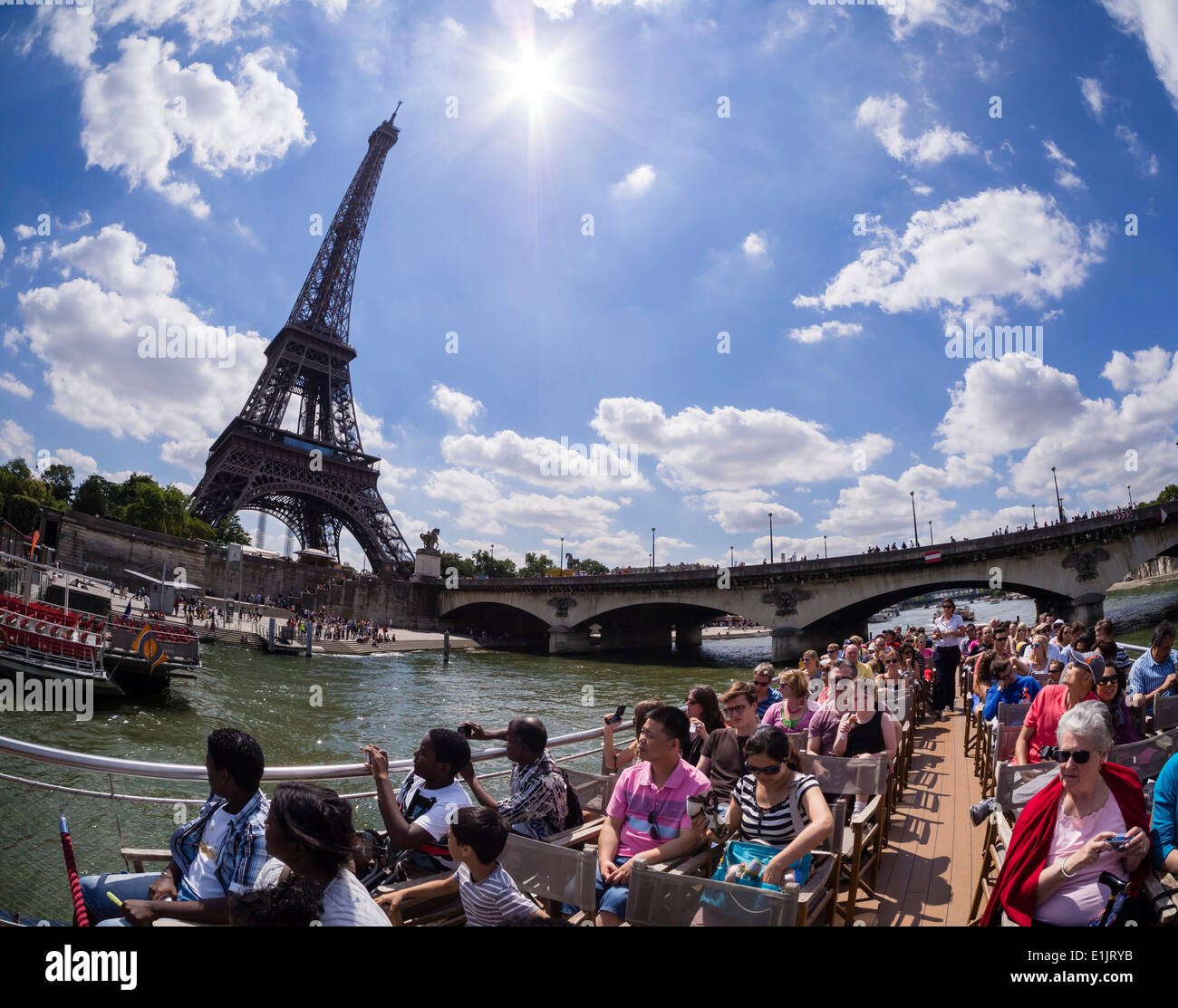 Tourists pass the Paris Eiffel Tower on a boat on the Seine river. - Stock Image