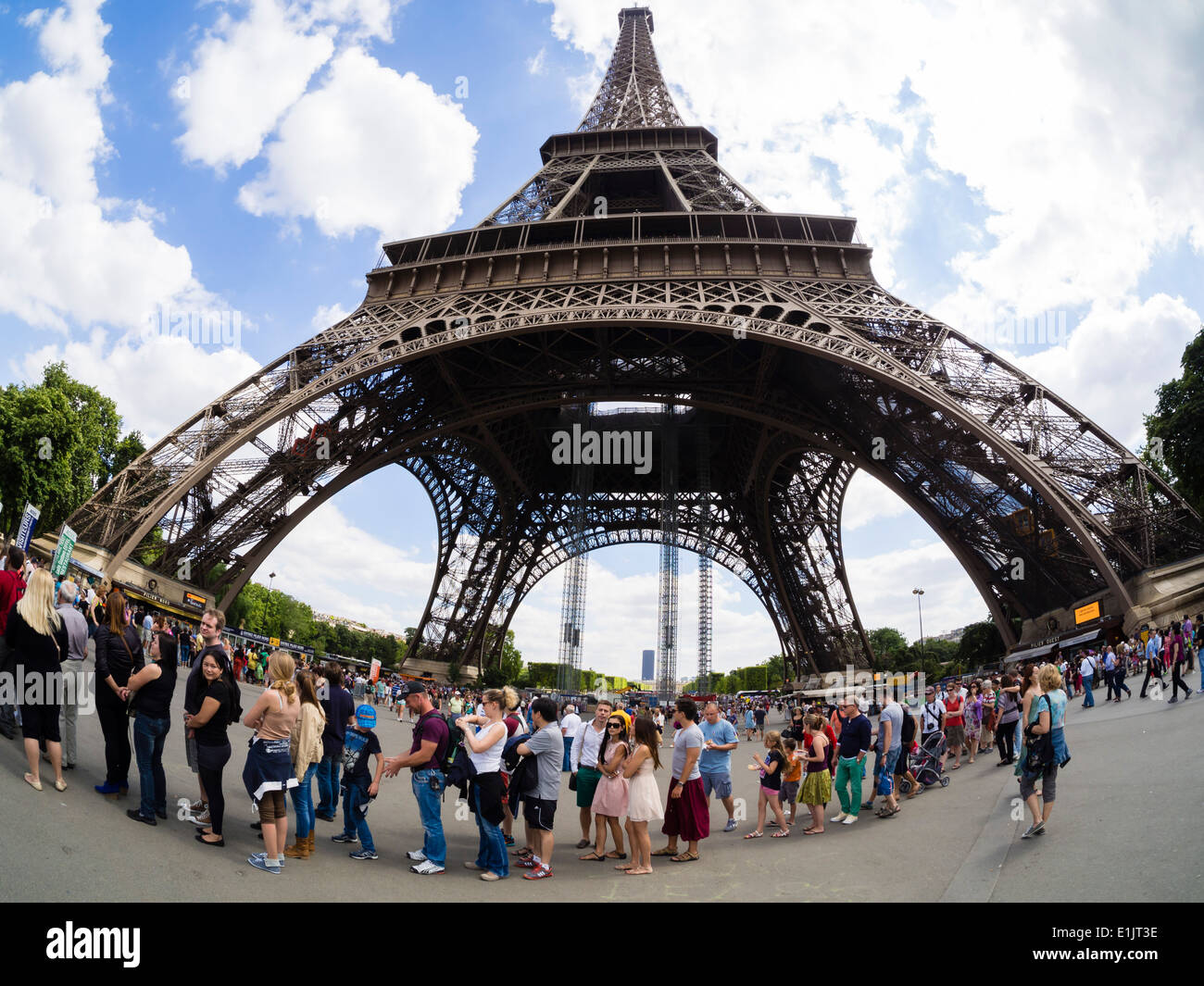 Tourists stand in a long line for the elevators at the Paris Eiffel Tower. - Stock Image