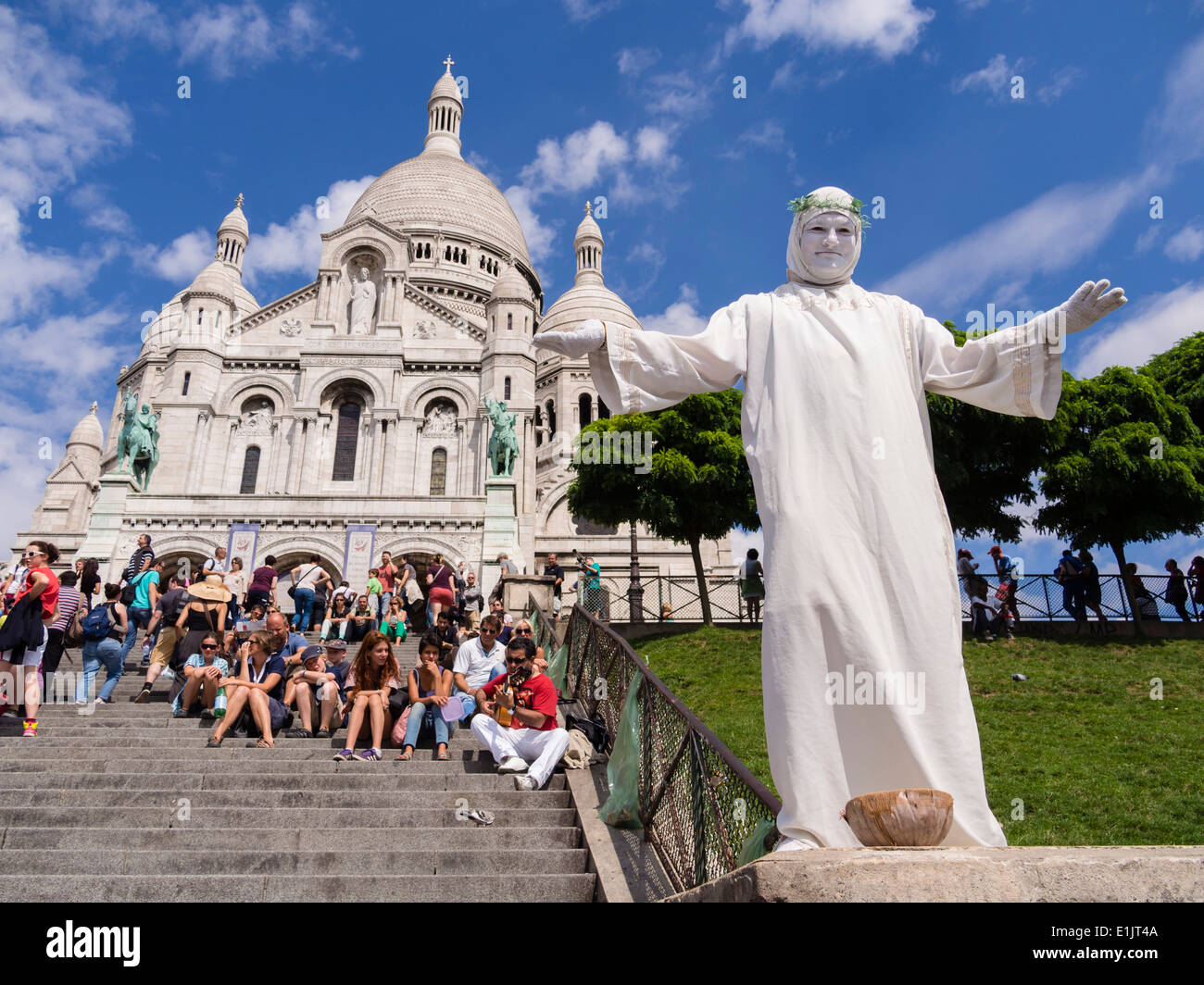 A street artist performs in front of the Basilica of the Sacre Coeur on the Montmartre hill in Paris. - Stock Image
