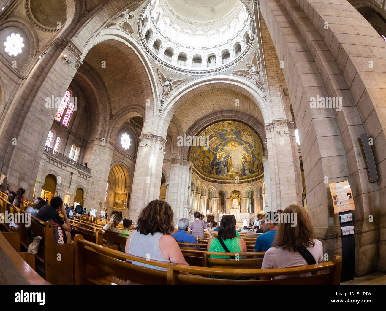 Tourists visit the Basilica of the Sacre Coeur on the Montmartre hill in Paris. Stock Photo
