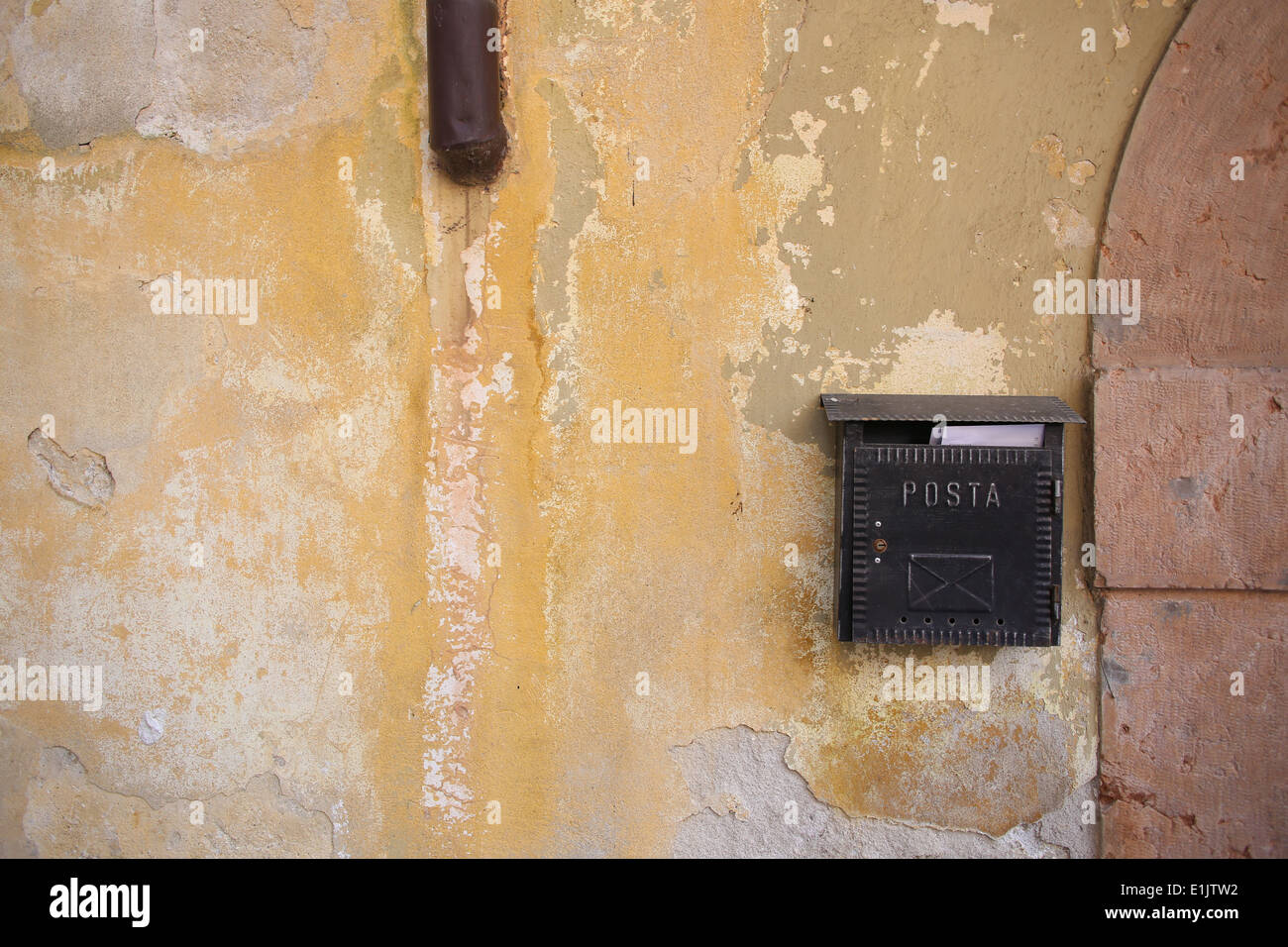 A residential 'Posta' postbox on the side of a peeling yellow wall, Italy. - Stock Image