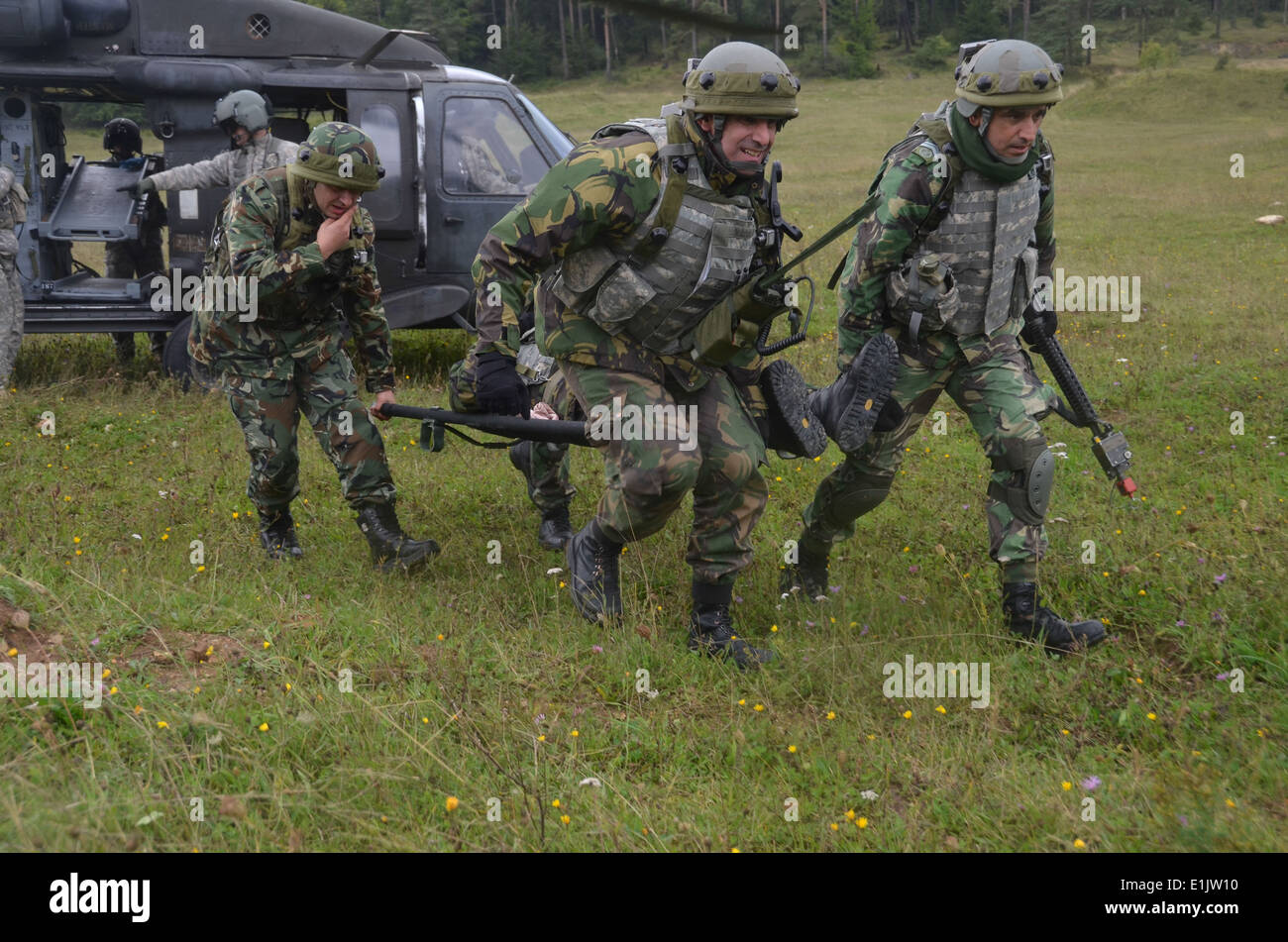 Portuguese soldiers with the 7th Portuguese National Contingency carry a simulated casualty from a U.S. Army UH Stock Photo
