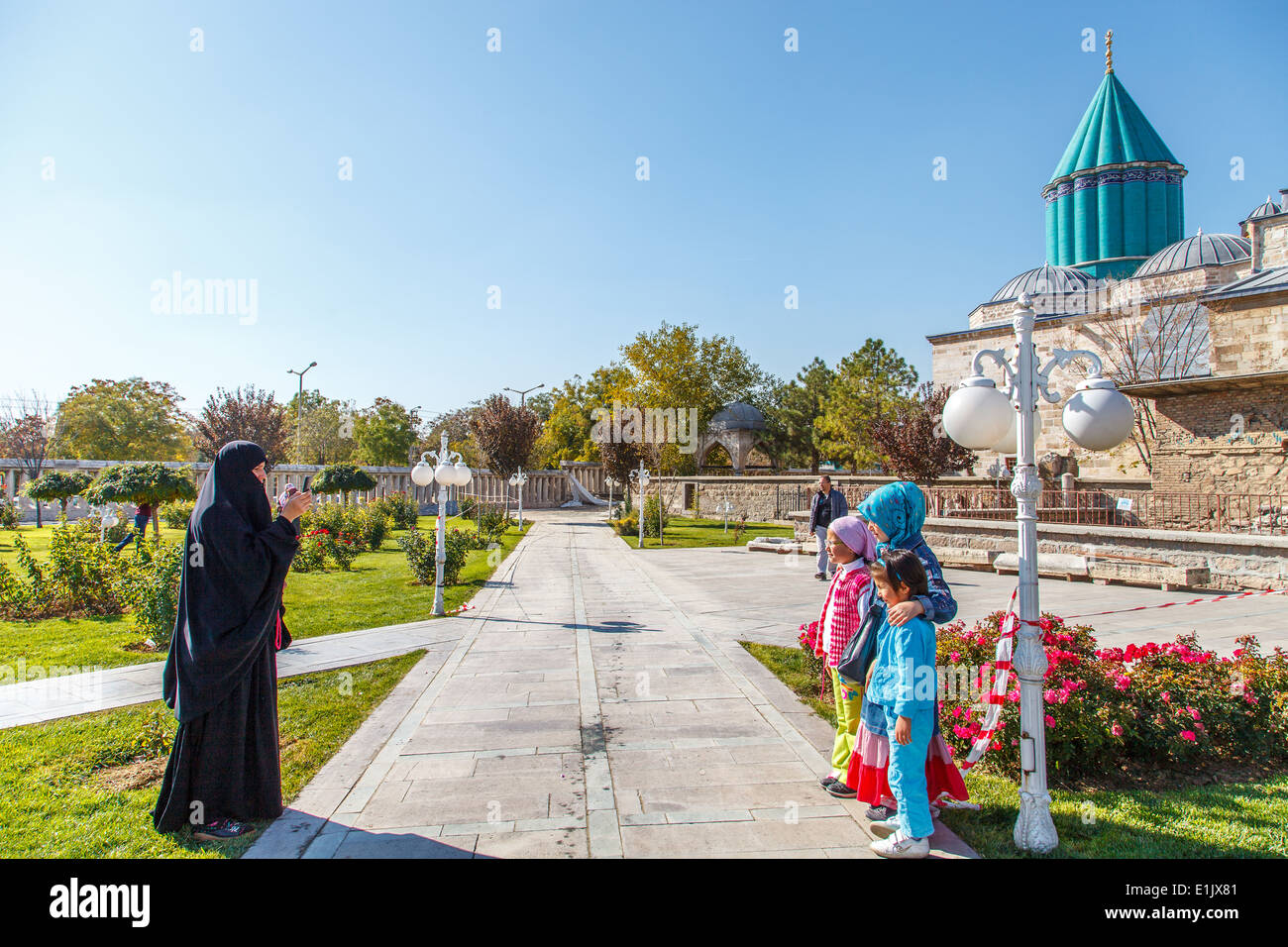 Mother taking picture of her sons in front of Mevlana museum Stock Photo