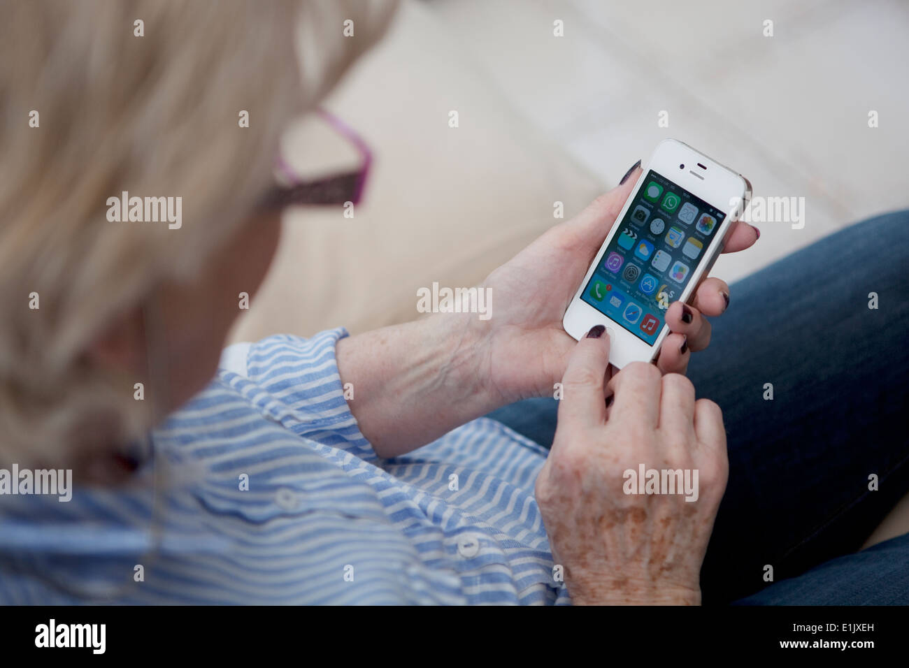 Mature woman embracing technology through use of a mobile smartphone. - Stock Image