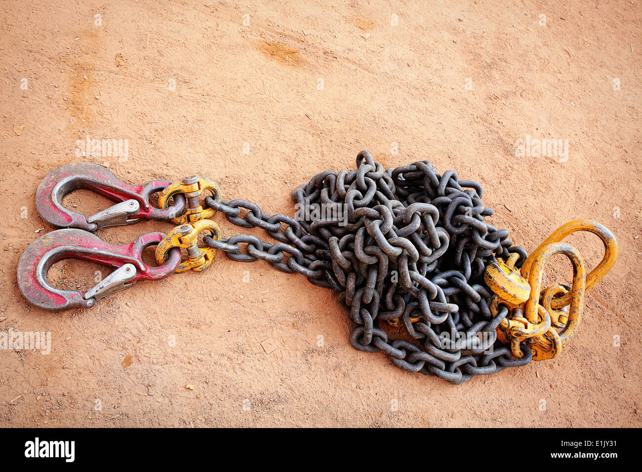 Industrial strength lifting chains and sling hooks in a heap on the ground - Stock Image