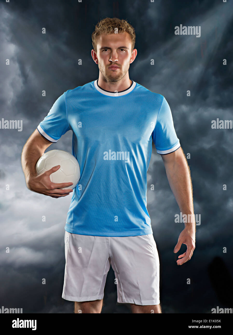 Professional football player poses against a storm cloud and stadium lights - Stock Image