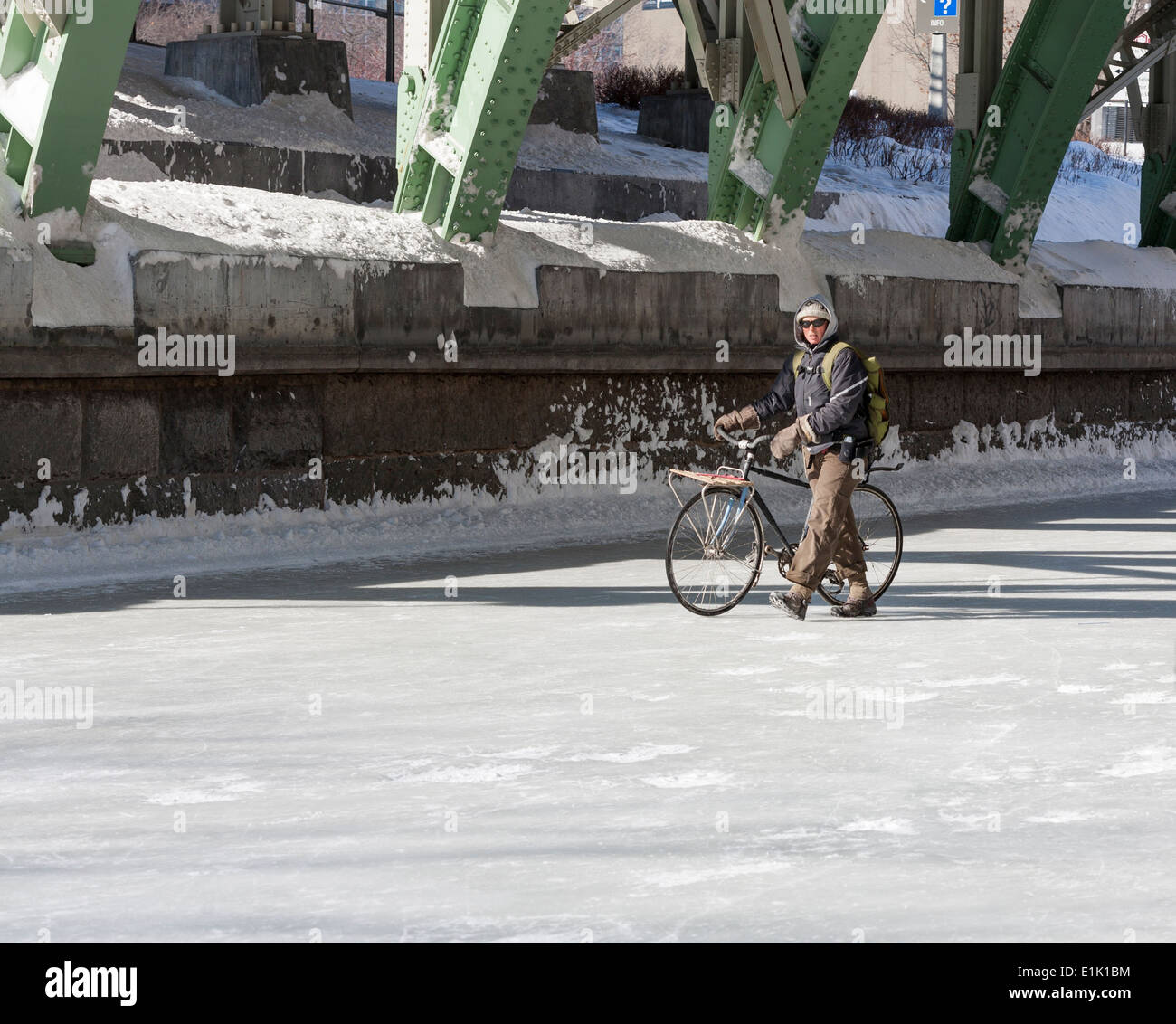 Winter Bicycle on the Frozen Rideau Canal. A cyclist walks his bike across a frozen Rideau Canal under the Mackenzie Bridge. - Stock Image