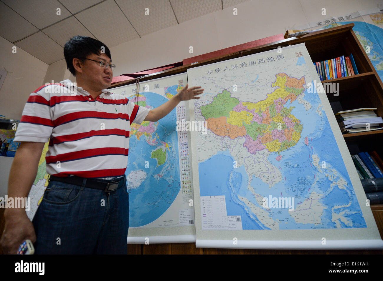 Changsha, China's Hunan Province. 23rd June, 2014. Lei Yixun, editor-in-chief of Hunan map publishing house shows a vertical atlas of China which is newly-issued by the publishing house in Changsha, capital of central China's Hunan Province, on June 23, 2014. Islands in South China Sea share the same scale with mainland and are better shown than traditional map. © Bai Yu/Xinhua/Alamy Live News - Stock Image