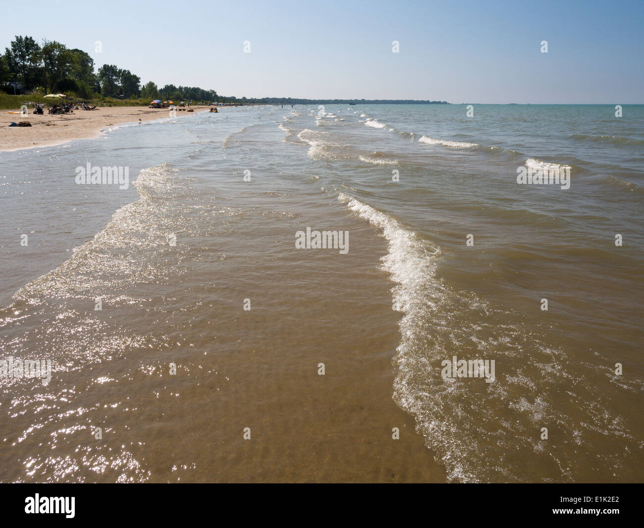 Summer at the Lake Huron beach. Gentle Waves roll in on Ipperwash Beach while sunbathers line the shore. - Stock Image