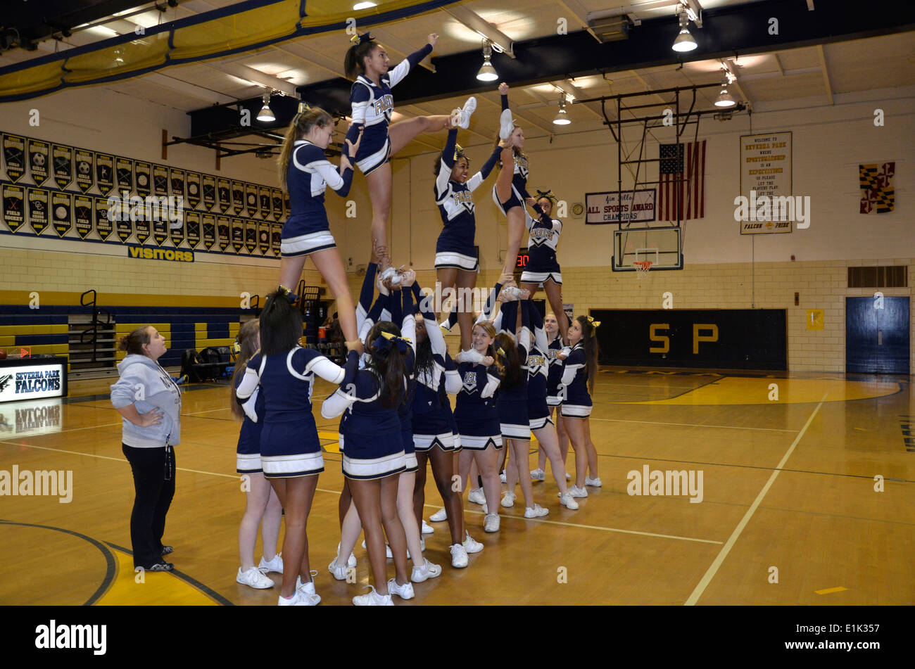 Cheerleaders perform during halftime at a high school basketball game - Stock Image