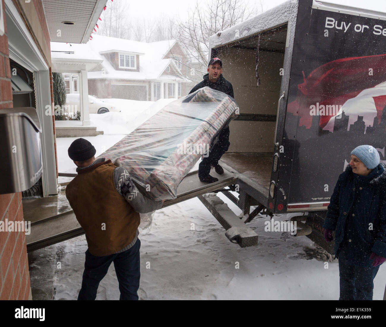 Moving in a Snow Storm. Two men lift a plastic wrapped couch into a moving van while the snow pours down. A woman looks on. - Stock Image