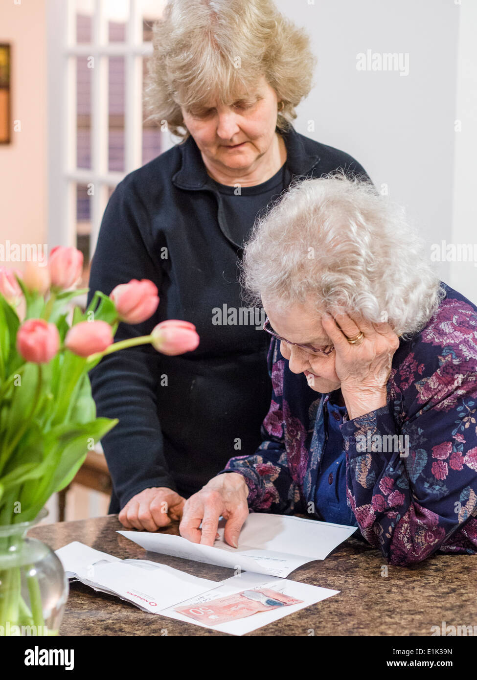 Reading the details of a Letter. A senior woman reads a letter, one hand following the text while the other supports Stock Photo