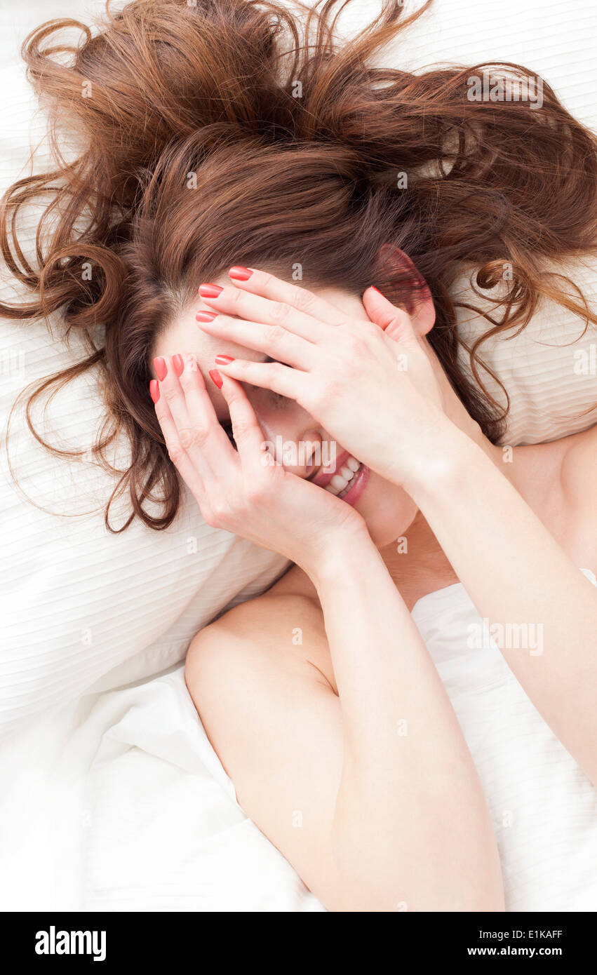 MODEL RELEASED Woman lying down with hands covering face smiling. - Stock Image