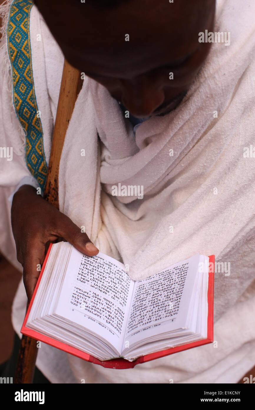 Faithful reading scriptures outside a Lalibela church - Stock Image