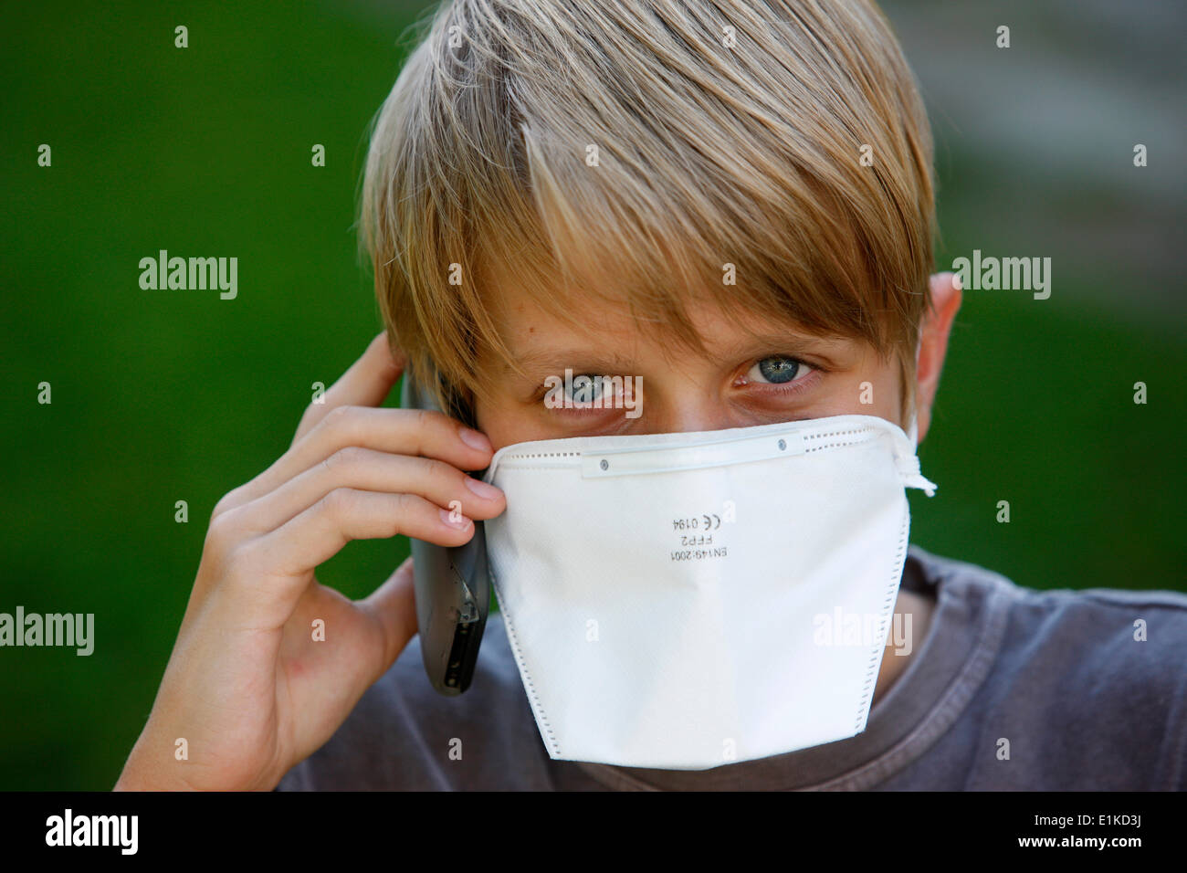 Boy wearing a respiratory mask and using a mobile phone - Stock Image