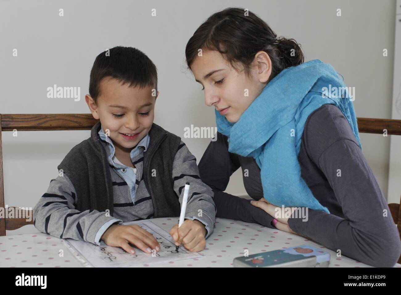 6-year-old boy writing with his sister - Stock Image