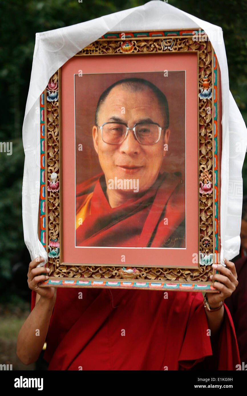 Buddhist holding a picture of the Dala• Lama - Stock Image
