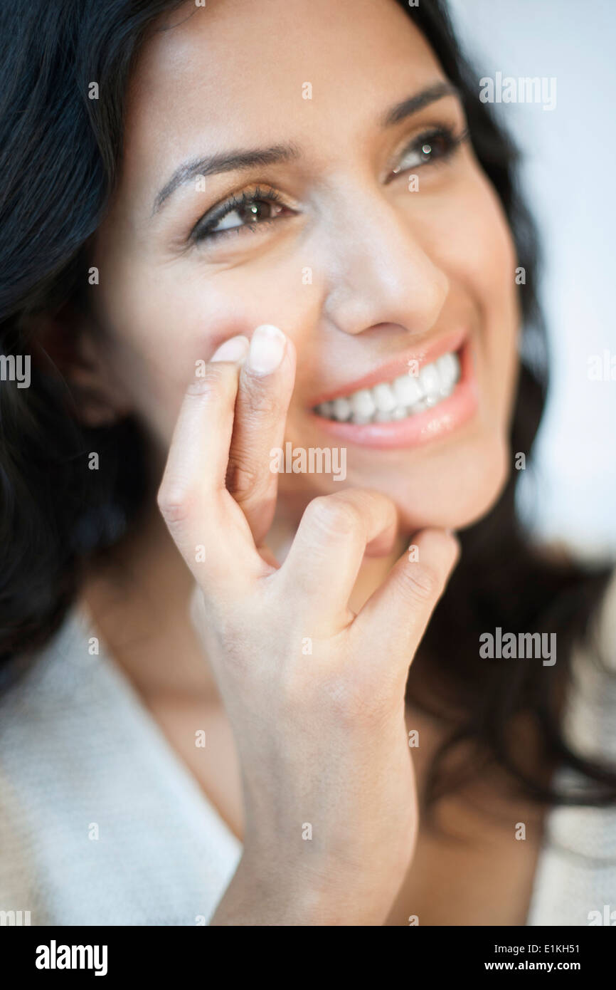 MODEL RELEASED Portrait of a woman with her fingers crossed. - Stock Image