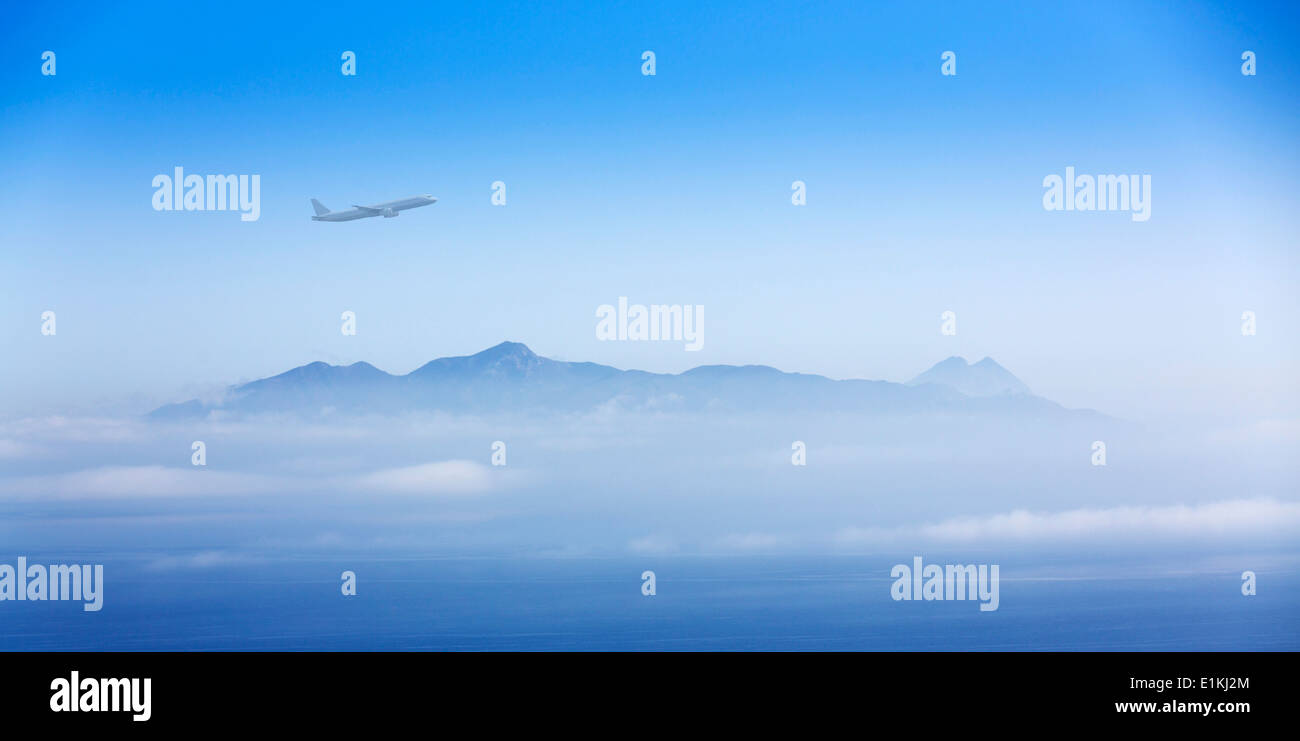 Aeroplane flying over the mountains. - Stock Image