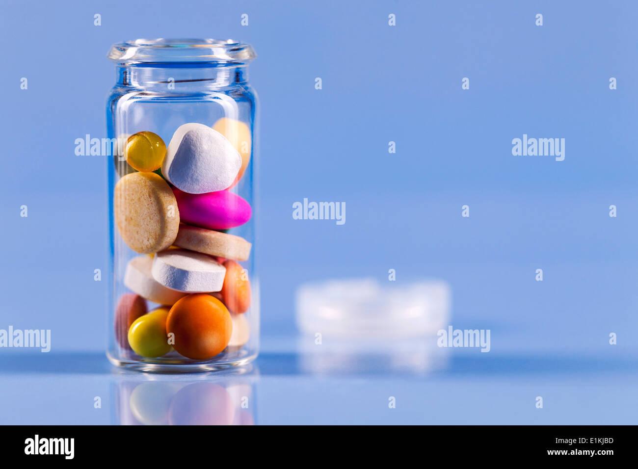 Pills and open bottle studio shot. - Stock Image