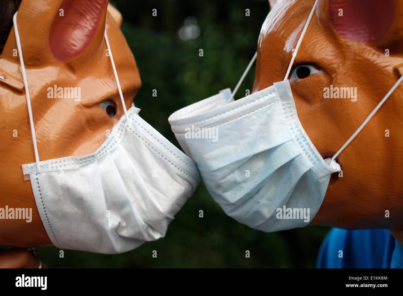 Children wearing pig masks and flu masks - Stock Image