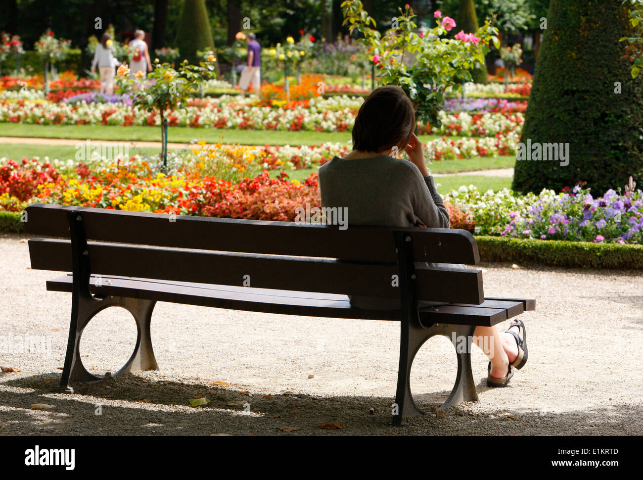 Woman siting on a bench - Stock Image