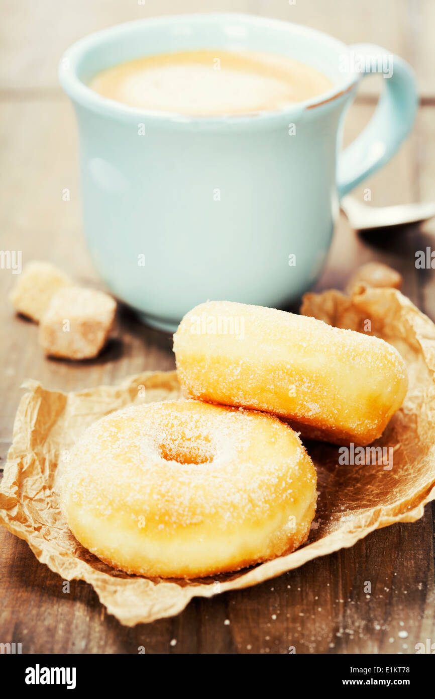 Coffee break with fresh sugary donuts over white background - Stock Image
