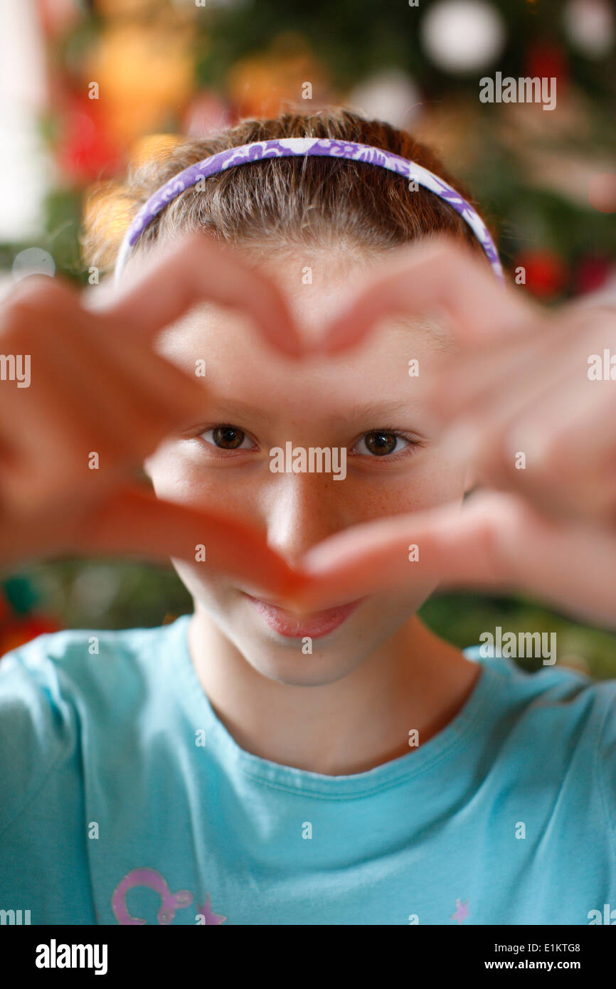 Girl making a heart shape with her fingers - Stock Image