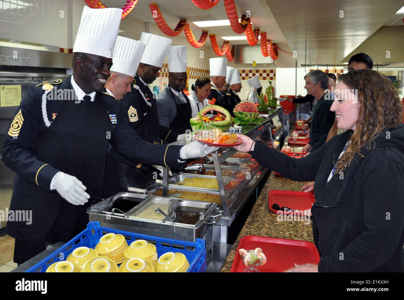 U.S. Army Command Sgt. Maj. Norriel Fahie, assigned to the Army Support Activity, serves Thanksgiving dinner to Stock Photo