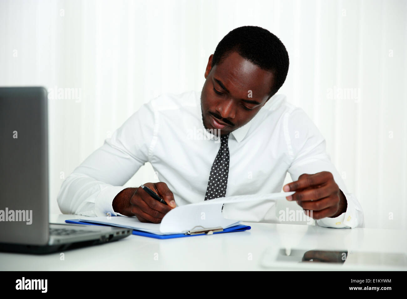 African man signing document in office - Stock Image