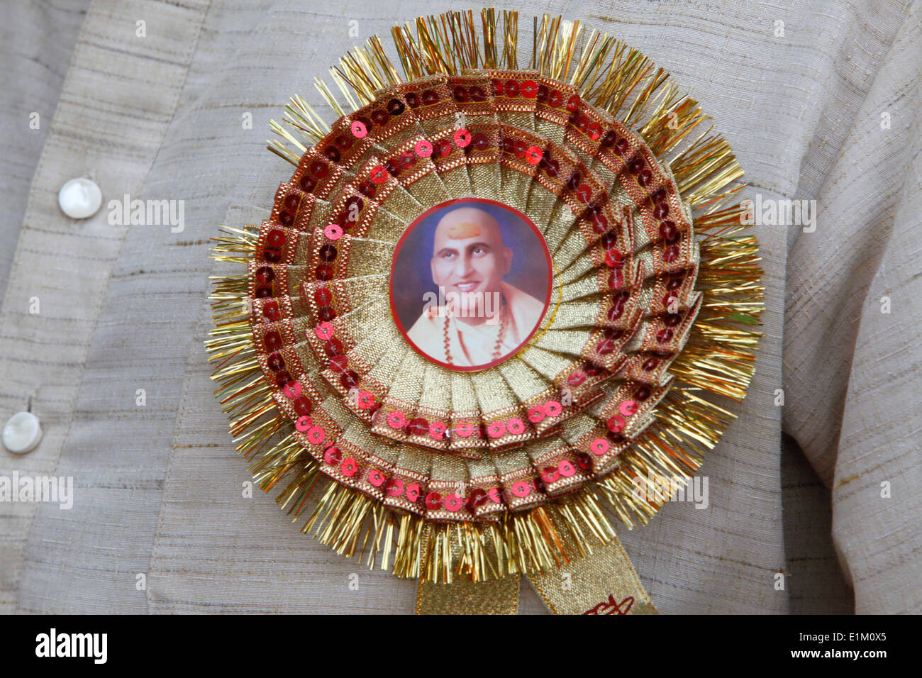 Devotee wearing a button with a portrait of spiritual leader Swami Avdeshanand Giri - Stock Image