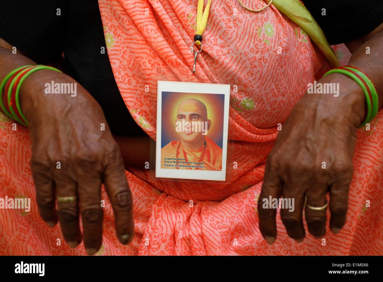 Devotee wearing a portrait of spiritual leader Swami Avdeshanand Giri - Stock Image