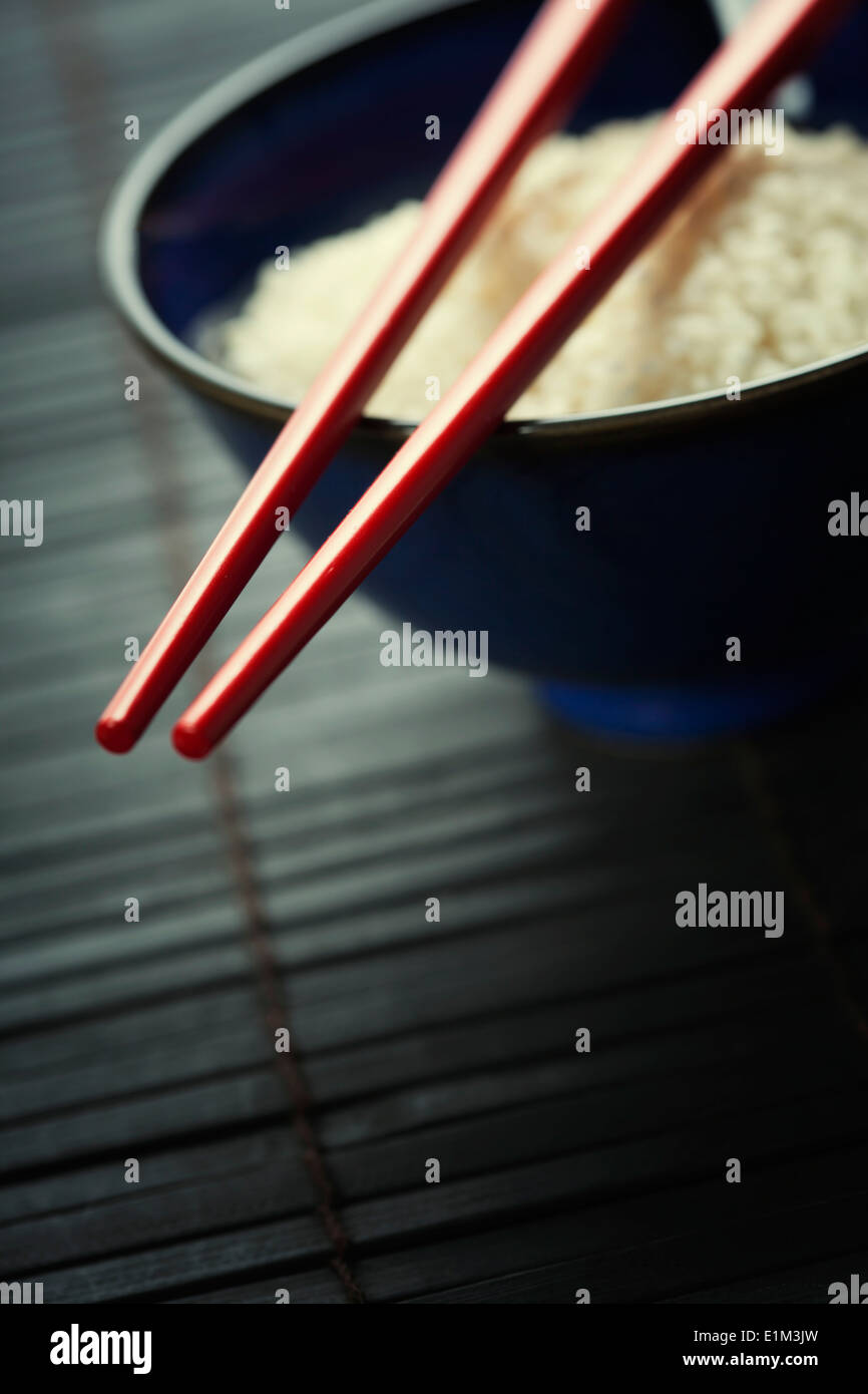 Bowl of rice and chopsticks over black - Stock Image